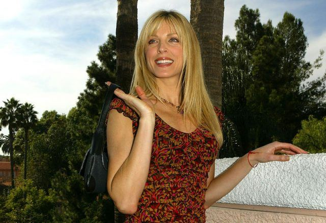 Marla Maples smiling as she holds a bag over her shoulder.