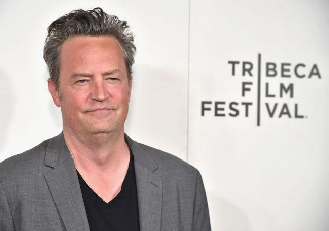 Matthew Perry posing in a grey suit and black shirt.