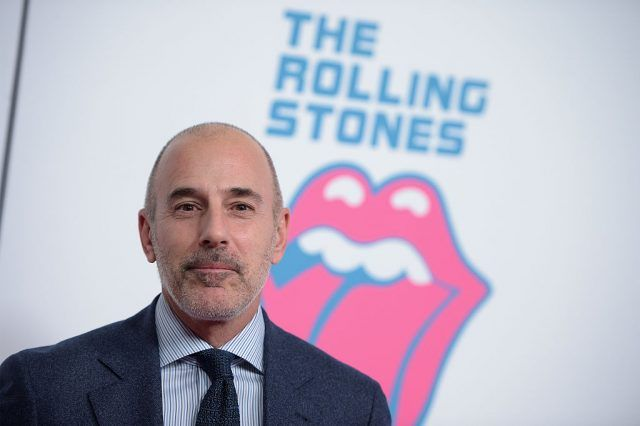 Matt Lauer in a black suit and tie on a red carpet.