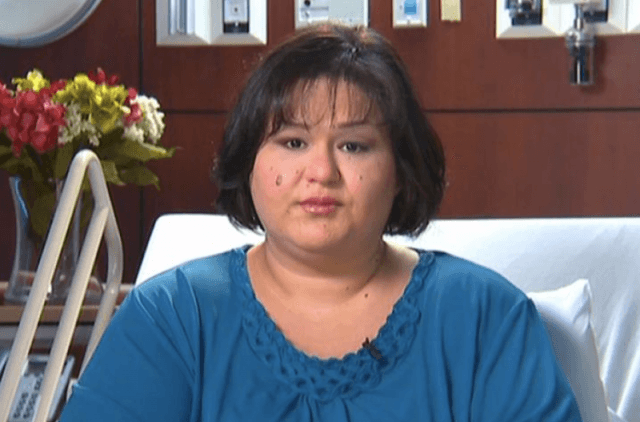 Mayra Rosales sits on her bed in a hospital.