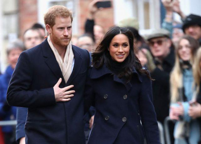Prince Harry and Meghan Markle walk closely together as they greet the public.
