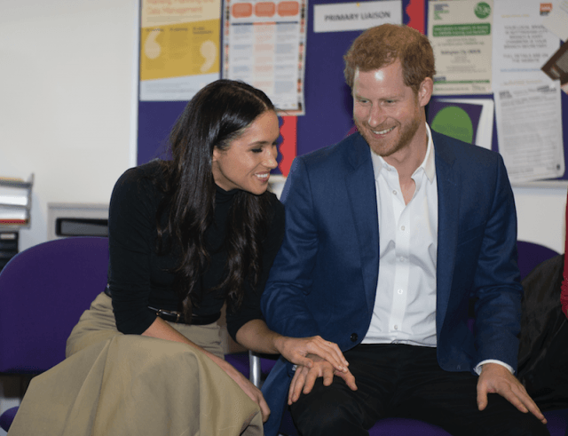 Meghan Markle holds Prince Harry's hand while they sit together and laugh.
