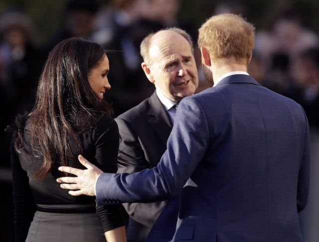Prince Harry touches Meghan Markle's back while having a conversation.