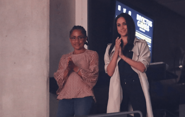 Meghan Markle and her mother applaud while watching a game.