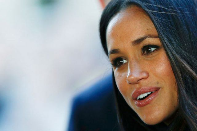 Meghan Markle smiles as she stands in front of a group of people.