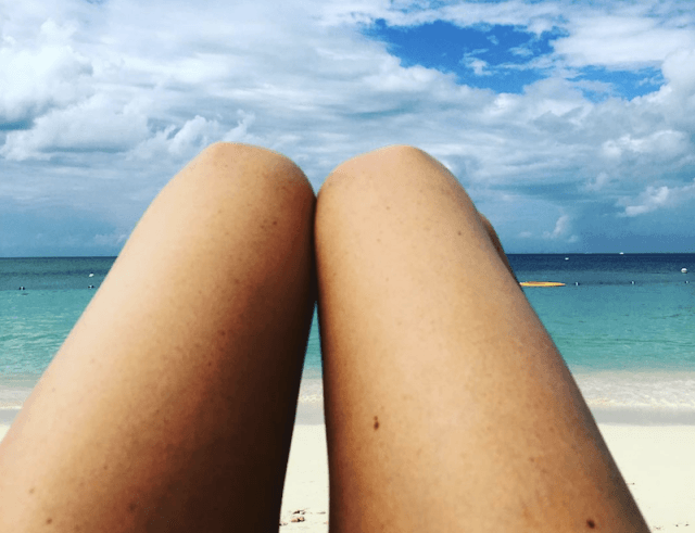 Meghan Markle's legs in front of a beach view.
