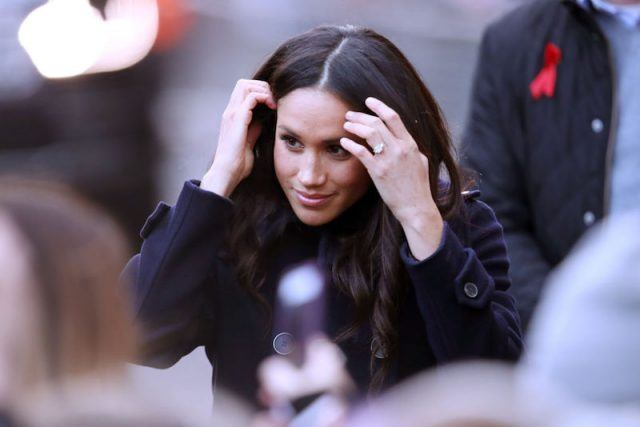 Meghan Markle pushing her hair back as she greets the public.