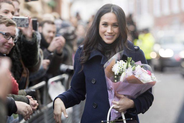 Meghan Markle smiles while holding flowers in front of fans.
