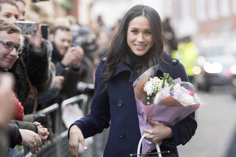 Meghan Markle smiling and holding a bouquet of flowers.