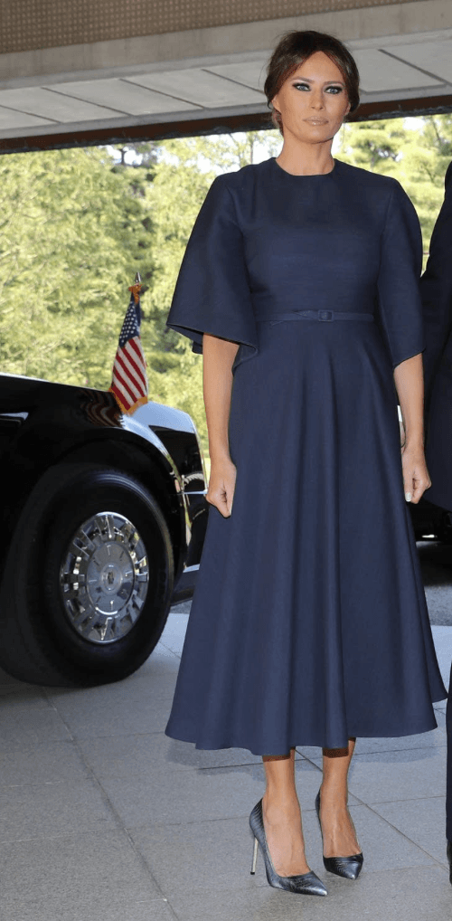 Melania Trump stands while wearing a navy dress and high heels.