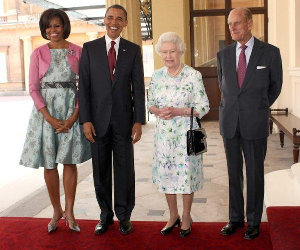 Barack Obama smiling with Michelle Obama as they stand next to Queen Elizabeth and Prince Phillip.