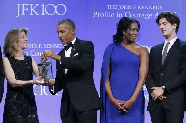 Michelle Obama stands next to Barack Obama as he accepts an award.