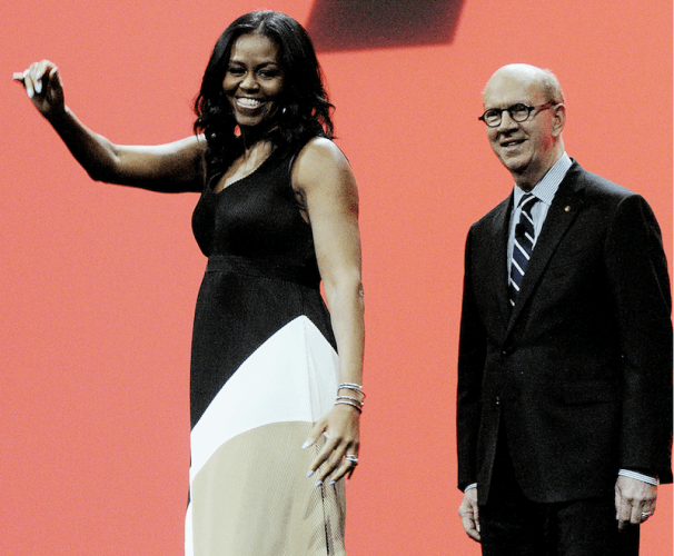 Michelle Obama on stage with a black, white and beige dress.