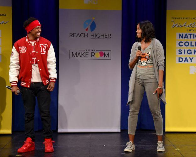 Michelle Obama stands on stage with Nick Cannon.