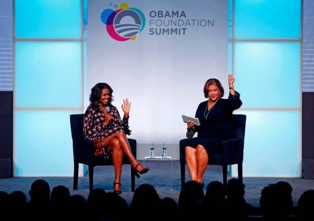 Michelle Obama sitting on a black chair and waving at the audience at the Obama Foundation Summit.