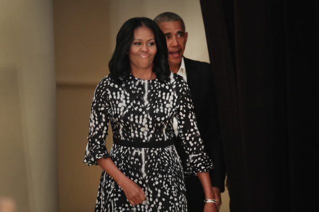 Michelle Obama walks in front of Barack Obama as she enters a stage.