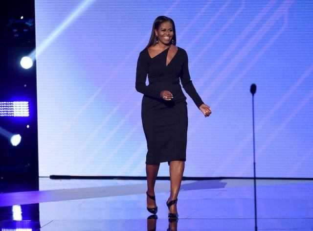 Michelle Obama walking on stage in a dress and heels.