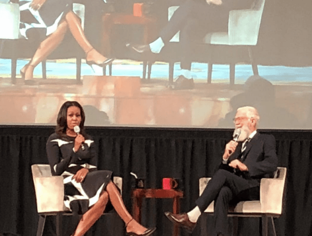 Michelle Obama sits on a white chair holding a microphone near her mouth.