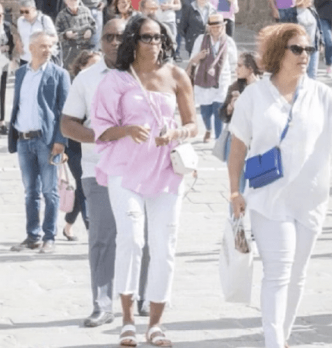 Michelle Obama in a pink top and white pants