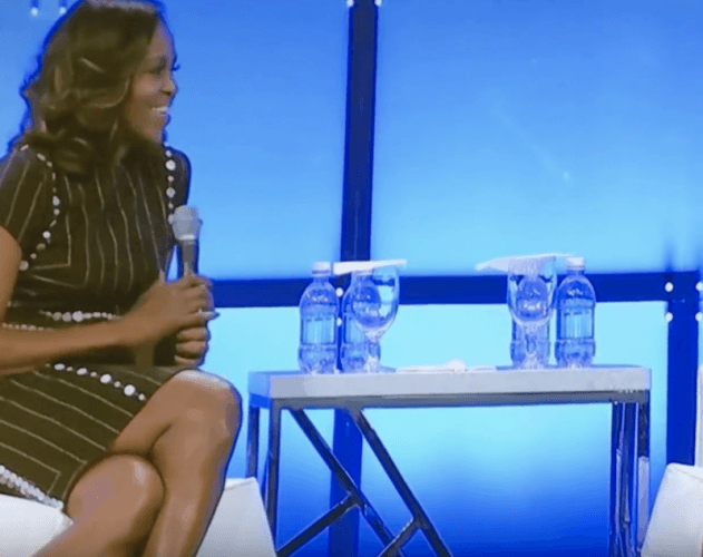 Michelle Obama sitting on a couch holding a microphone.