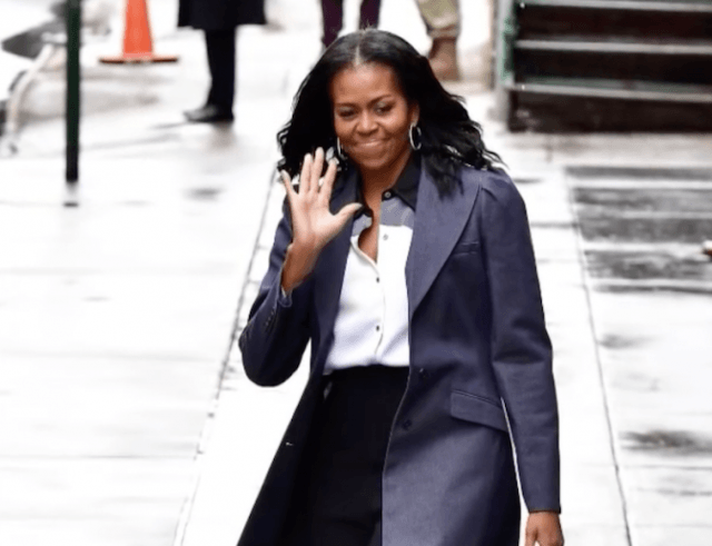 Michelle Obama waves and smiles while walking down the street.