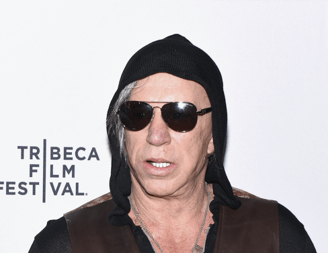 Mickey Rourke on a red carpet wearing a hoodie and sunglasses.