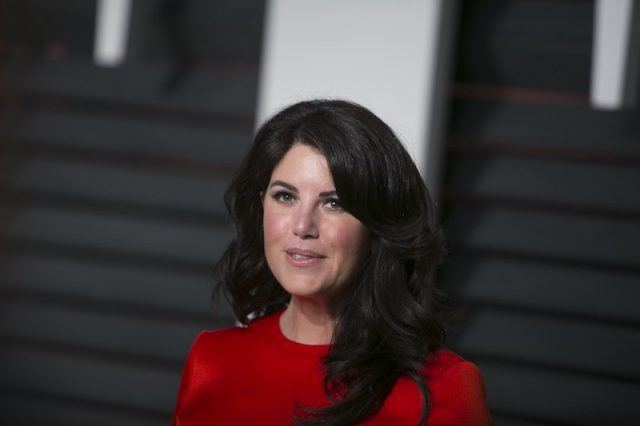 Monica Lewinsky stands in a red dress.
