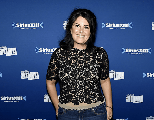 Monica Lewinsky posing in a black lace shirt and jeans.