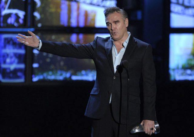 Morrissey sticks one arm out while holding an award in the other while standing on stage.