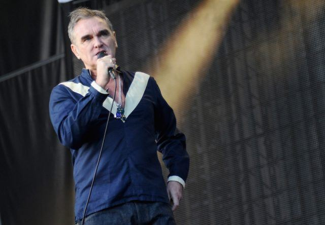Morrissey performs while holding a microphone.