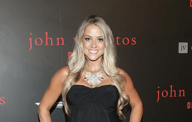 Nicole Curtis smiles in a black dress.