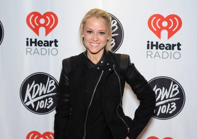 Nicole Curtis posing in front of a backdrop.