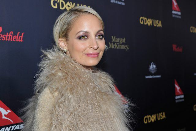 Nicole Richie smiles in a fur jacket on a red carpet.