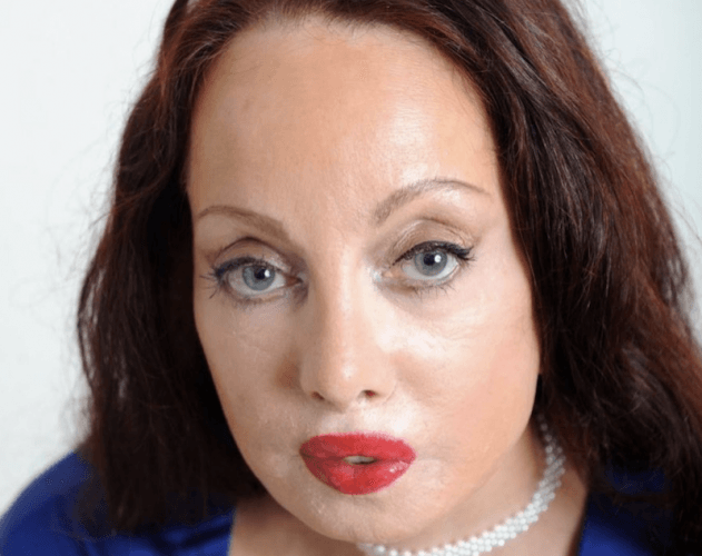Nileen Namita wearing red lipstick and a pearl necklace.