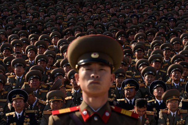 A North Korean soldiers stands before spectators during a mass military parade.