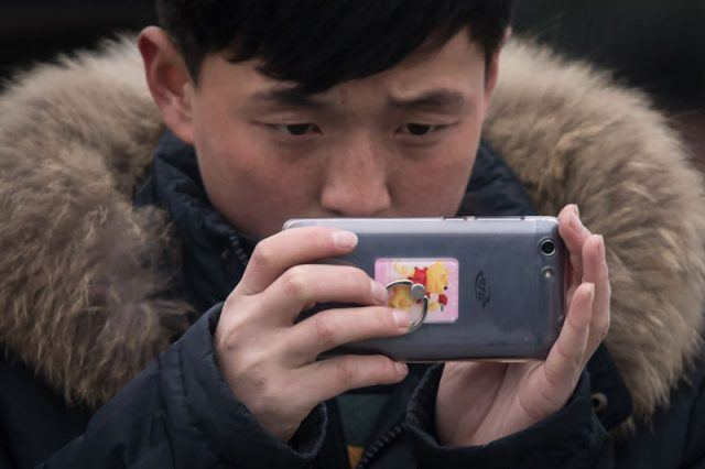 A man takes a photograph with a cell phone.