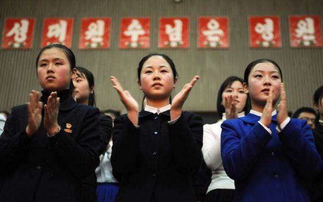 A group of young teens clapping their hands.