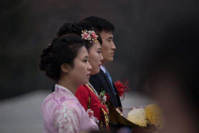 A group of people walk with flowers.