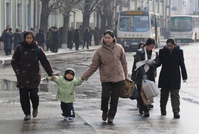 North Koreans walk along a street in the winter.
