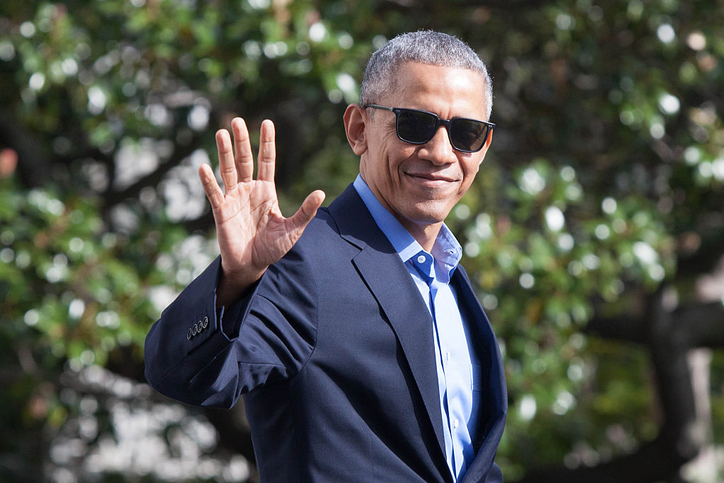 President Barack Obama waves as he exits The White House wearing sunglasses