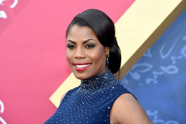 Omarosa Manigault posing in a blue dress and smiling.