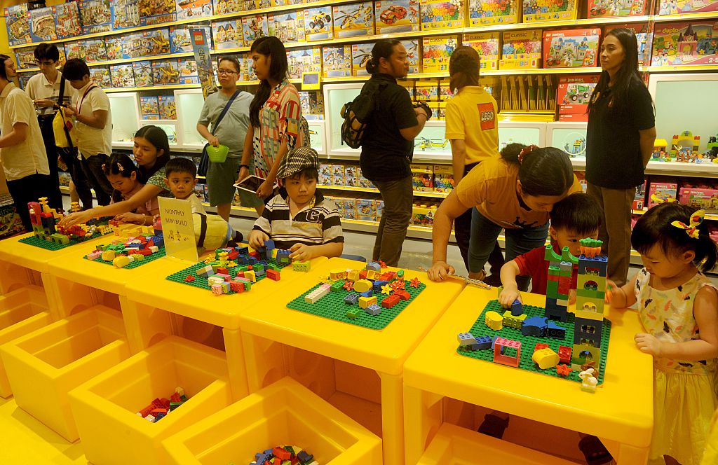 Children play with Lego blocks during the opening of the brand's first certified store