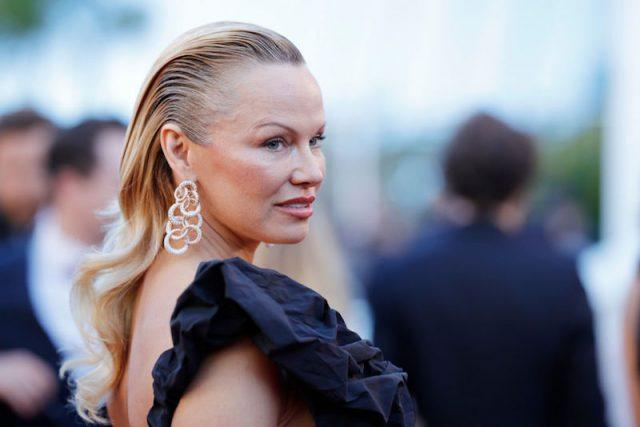 Pamela Anderson poses in a ruffled gown and silver earrings.
