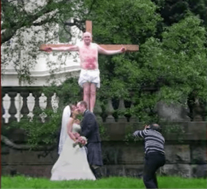 Bride and groom kissing in front of man on cross