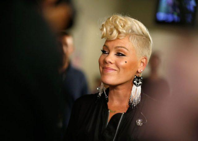 Pink smiling while wearing a black jacket and cat-themed earrings.