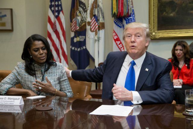 Omarosa Manigault Newman sits with Donald Trump as he reaches for her back.