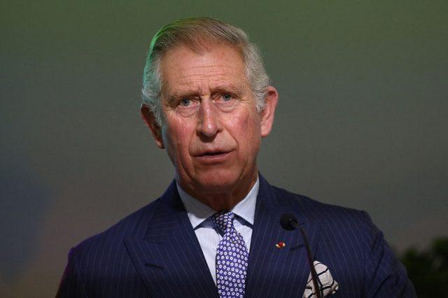 Prince Charles stands in front of a microphone in a suit and tie.