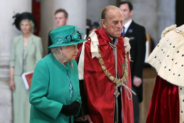 Queen Elizabeth stands next to Prince Charles as they attend a service at a cathedral.