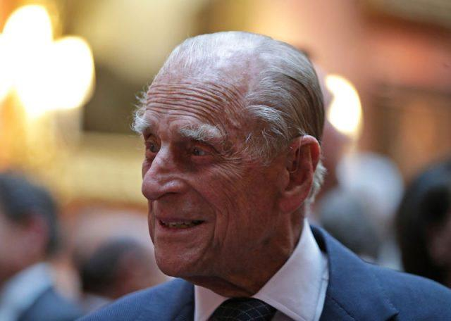 Prince Phillip looking to the side and smiling while wearing a suit and tie.