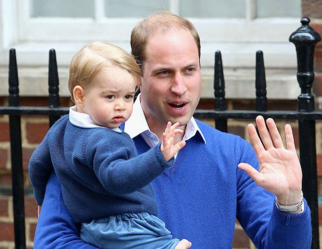Prince George and Prince William waving at a crowd.